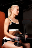Beautiful sexy athlete with dumbbells. Portrait of a blond sportswoman holding weights on her knees Stock Photography