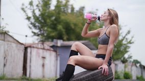 Beautiful athletic young blond woman in top and shorts sitting on tires and drinking water from a bottle, after a stock video