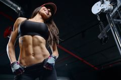 Sexy athletic young girl training abs in gym. Beautiful sexy athletic young brunette Caucasian girl working out training pumping up abdominal muscles abs Royalty Free Stock Photography
