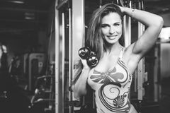 Sexy athletic young girl training arms in gym. Beautiful sexy athletic young caucasian girl working out training arms in the gym gaining weight pumping up Royalty Free Stock Photography