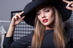 Beautiful sexy attractive girl in a black hat with red lipstick in fashion photography in a black dress with a bright evening make Royalty Free Stock Photos