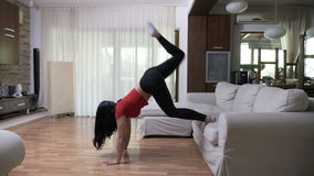 Beautiful attractive young woman doing morning exercise to stay in shape. At home stock video footage