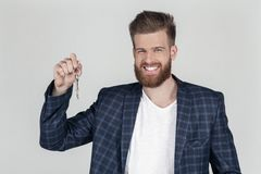 A beautiful sexy bearded business man in a jacket looks happy at the camera and holds the keys in his hand. he bought a new stock photos