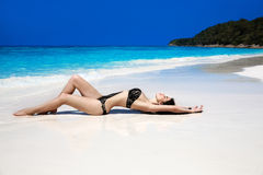 Beautiful sexy bikini model woman lying on exotic tropical beach Royalty Free Stock Images