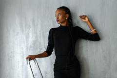 Beautiful and sexy black woman in dark dress posing looking away leaning hand on gray wall at studio Stock Photography