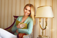 Beautiful sexy blond business woman reading book relax. Beautiful young sexy blond girl with makeup woman dressed in a trendy, stylish clothing collection Royalty Free Stock Images