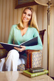 Beautiful sexy blond business woman reading book relax. Beautiful young sexy blond girl with makeup woman dressed in a trendy, stylish clothing collection Royalty Free Stock Photo