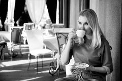 Beautiful sexy blond business woman restaurant drink coffee tea Royalty Free Stock Photo