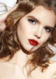 Beautiful sexy blond girl with make up red lips. Closeup of the face belong to beautiful young sexy blonde girl with curly hair pure snow white skin and bright Stock Image