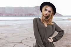 Beautiful, sexy blond girl posing in the mountains on a cracked ground in a black hat with bright make-up Royalty Free Stock Image