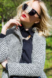 Beautiful sexy blond girl with red lips in sunglasses walking in the garden of a bright sunny day Stock Photography
