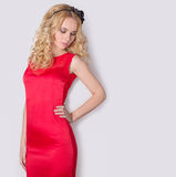 Beautiful sexy blond girl in red long evening dress with flowers in her hair and curls hairstyle Royalty Free Stock Photography