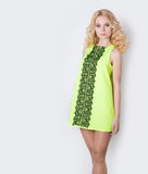 Beautiful blond girl in a yellow summer dress with hair curls Stock Photos