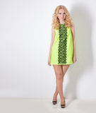 Beautiful blond girl in a yellow summer dress with hair curls Stock Photo