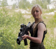 Beautiful sexy blond woman holding army weapon Royalty Free Stock Images