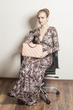 Beautiful sexy blond woman sitting on chair holding fashion bag Royalty Free Stock Photo