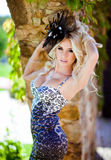 Beautiful blonde with big bust in leopard print dress and a. Hat with feathers standing against the wall of rock in the summer royalty free stock image