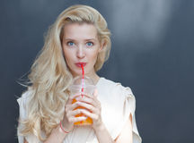 Beautiful sexy blonde with blue eyes drinking beverage through a straw on a hot summer day near the wall Royalty Free Stock Photo