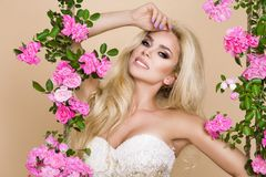 Beautiful blonde bride in a wedding dress on a swing decorated with roses. Beautiful blonde bride woman model in a wedding dress on a swing decorated with roses stock photos