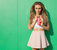 Beautiful sexy blonde with dreads and blue eyes drinking beverage through a straw on a hot summer day near the greem wall Royalty Free Stock Photos