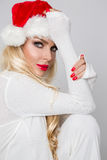 Beautiful blonde female model dressed as Santa Claus in a red cap Stock Images
