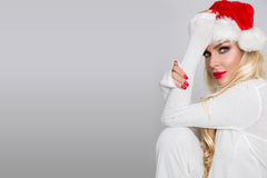 Beautiful sexy blonde female model dressed as Santa Claus in a red cap Stock Photos
