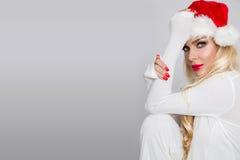 Beautiful blonde female model dressed as Santa Claus in a red cap Stock Photos