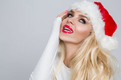 Beautiful sexy blonde female model dressed as Santa Claus in a red cap Royalty Free Stock Photos