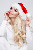Beautiful sexy blonde female model dressed as Santa Claus in a red cap Royalty Free Stock Photo