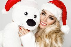 Beautiful blonde female model dressed in a Santa Claus hat embraces a white teddy bear in a red cap Christm. Beautiful blonde female model dressed in a Santa stock photography