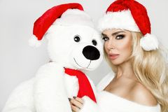 Beautiful blonde female model dressed in a Santa Claus hat embraces a white teddy bear in a red cap Christm. Beautiful blonde female model dressed in a Santa royalty free stock images