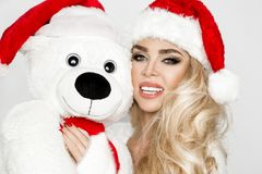 Beautiful blonde female model dressed in a Santa Claus hat embraces a white teddy bear in a red cap Christm. Beautiful blonde female model dressed in a Santa stock images