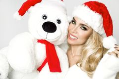 Beautiful blonde female model dressed in a Santa Claus hat embraces a white teddy bear in a red cap Christm. Beautiful blonde female model dressed in a Santa stock photos