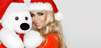Beautiful blonde female model dressed in a Santa Claus hat embraces a white teddy bear in a red cap Christm. Beautiful blonde female model dressed in a Santa stock photo