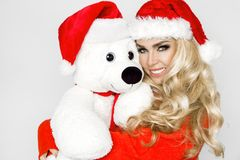 Beautiful blonde female model dressed in a Santa Claus hat embraces a white teddy bear in a red cap Christm. Beautiful blonde female model dressed in a Santa stock image