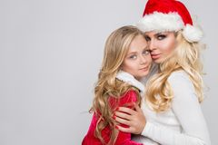 Beautiful blonde female model mother and daughter dressed as Santa Claus in a red cap with at the White Royalty Free Stock Photo