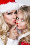 Beautiful blonde female model mother and daughter dressed as Santa Claus in a red cap Stock Photo