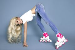 Beautiful sexy blonde female model roller girl dressed in jeans and summer clothes and roller Royalty Free Stock Photography