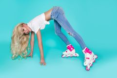 Beautiful sexy blonde female model roller girl dressed in jeans and summer clothes and roller Royalty Free Stock Image