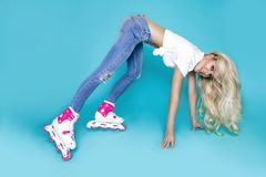 Beautiful sexy blonde female model roller girl dressed in jeans and summer clothes and roller Royalty Free Stock Photos