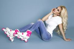 Beautiful sexy blonde female model roller girl dressed in jeans and summer clothes and roller Stock Images