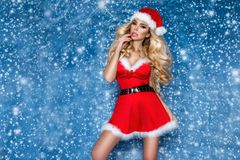 Beautiful blonde female model dressed in a Santa Claus hat and dress. Sensual girl for Christmas. royalty free stock photography