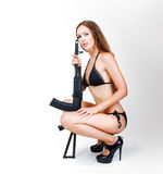 Beautiful blonde girl in bikini holding airsoft gun. (rifle) sitting in studio on white background royalty free stock images