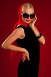 Beautiful blonde girl in black dress. On red background stock images