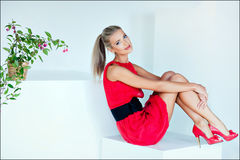 Beautiful sexy blonde girl with blue eyes in a red dress sitting. On a white cube in the Studio Stock Photography