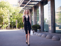 Beautiful blonde girl in casual clothes with perfect figure walking around the city. Fashion and city style. Black stylish to royalty free stock image