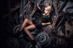 Beautiful sexy blonde girl in garage lying on disassembled car p Stock Photo