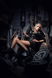 Beautiful sexy blonde girl in garage lying on disassembled car p Royalty Free Stock Image