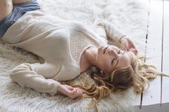 Beautiful blonde girl lying near the window. Weekend at hom stock image