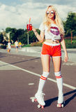 Beautiful blonde girl posing on a vintage roller skates in pink shorts and white T-shirt with a drink in a glass on a warm su Stock Image